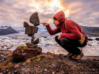 Man balances rocks as art